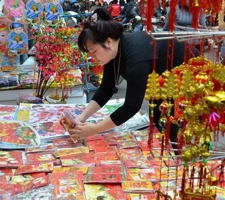 Một người phụ nữ bán bao lì xì và các đồ trang trí trên đường phố Hà Nội. (Ảnh: