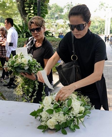 Hai người phụ nữ, đặt hoa và bưu thiếp bên ngoài phủ