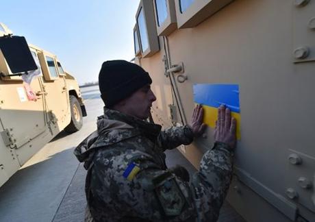Một quân nhân Ukraine đang dán cờ nước này lên chiếc xe bọc thép mới nhận. (Ảnh: