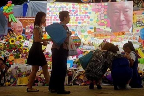 Ba mẹ con đang khóc thương cho nhà lãnh đạo Lý Quang Diệu khi đặt hoa tại một đài tưởng niệm.