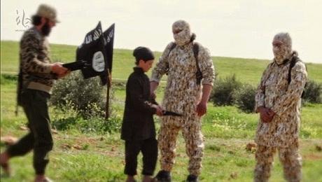 Một cậu bé đưa dao cho các đao phủ của IS. (Ảnh: