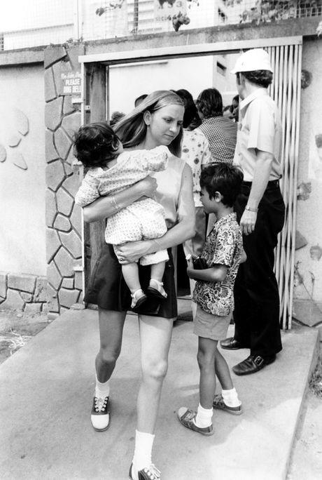 Một tình nguyện viên người Mỹ bế một em bé từ một cô nhi viện ra sân bay rời Việt Nam.