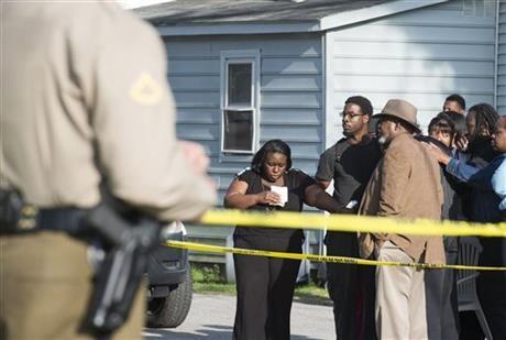 Những người hàng xóm đang đứng phía ngoài ngôi nhà hiện trường vụ tai nạn. (Ảnh: