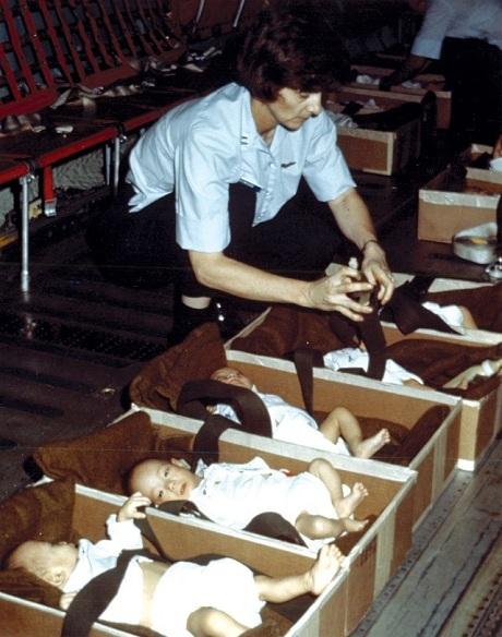 Một nhân viên người Mỹ đặt các em nhỏ vào từng hộp trước khi đem lên máy bay. (Ảnh: