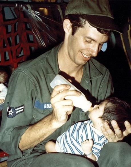 Một phụ nữ Mỹ bế một em nhỏ trên chuyến bay rời khỏi Việt Nam. (Ảnh: