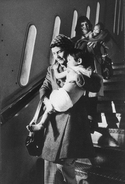 Một phụ nữ bế một em bé Việt Nam xuống máy bay đến Mỹ.
