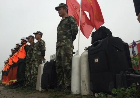 Các thợ lặn và binh lính chuẩn bị các trang thiết bị trước khi xuống sống cứu hộ. (Ảnh: