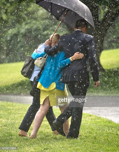 Tổng thống Obama lịch thiệp che ô cho hai nữ chính trị gia đi qua bãi cỏ phía nam Nhà Trắng.