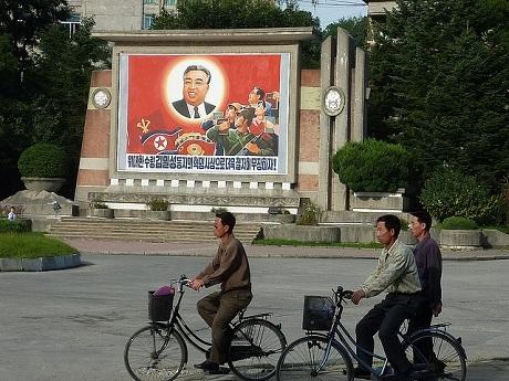Người dân đạp xe ngang qua bức áp phích có hình cố chủ tích Kim Nhật Thành. (Ảnh: