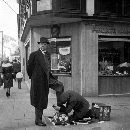 Cậu bé đánh giày làm lụng vất vả để kiếm một vài xu.