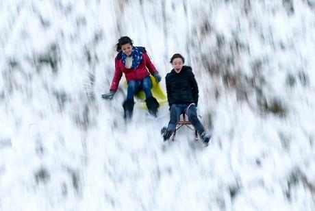 Bỉ: Các em nhỏ ngồi xe trượt tuyết và trượt từ trên đỉnh đồi xuống.
