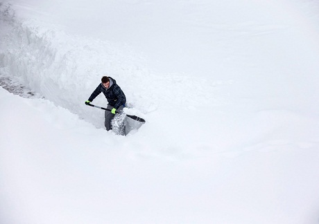 Đức: Một thanh niên dọn tuyết để lấy lối đi.