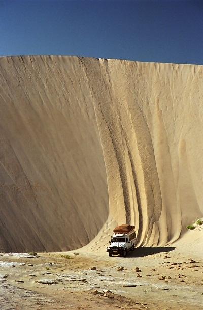 Lái xe xuống một đồi cát ở vịnh Lucky, Úc.