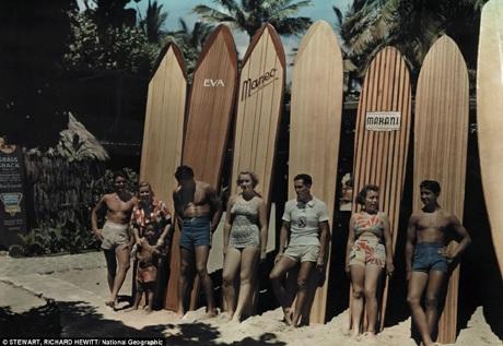 Một nhóm những người lướt sóng trên bãi biển Waikiki ở Hawaii đang tạo dáng bên ván trượt.