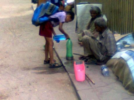 Một cậu bé Ấn Độ đang trút nước từ chai của mình sang chai của những người vô gia cư trên phố.