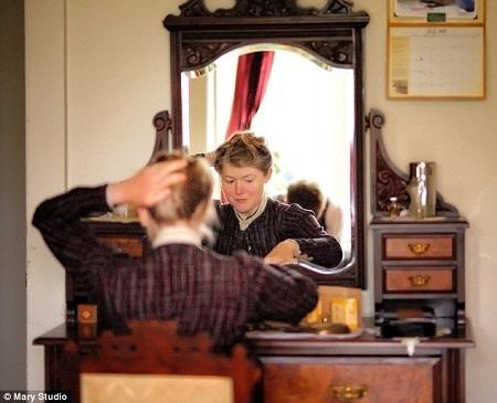 Một bàn trang điểm với thiết kế cổ. Cô Chrisman đang dùng kẹp vấn tóc theo lối xưa.