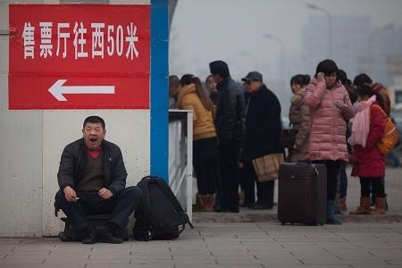 Một người đàn ông ngồi ngáp bên hàng dài những người đang chờ mua vé tàu.