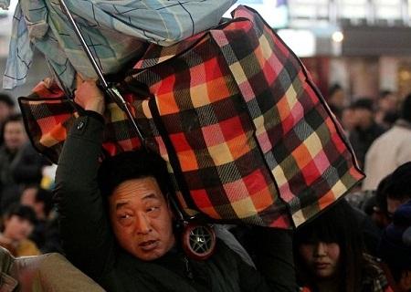 Một người đàn ông công kênh hết hành lý lên vai để dễ bề di chuyển trong sân ga chật cứng người.