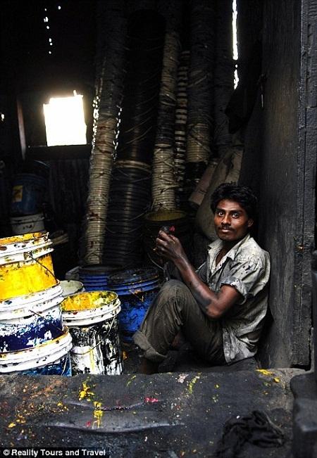 Một người đàn ông làm việc trong xưởng sản xuất sơn.