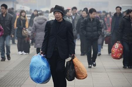 Một cô gái đeo khẩu trang đứng trước nhà ga ở thành phố Bắc Kinh.