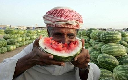 Một người đàn ông tận hưởng miếng dưa hấu mát lành ở chợ tại Dhahran, Ả Rập Saudi. (Ảnh: AFP).