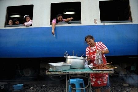 """Một người bán thịt xiên nướng ở Thái Lan """"cắm chốt"""" ven đường tàu. (Ảnh: Christopher Archambault)"""
