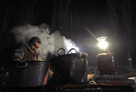 Người đàn ông Kashmir cặm cụi với quán ăn đêm. (Ảnh: Tauseef Mustafa)