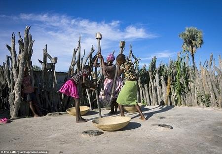 Phụ nữ trong bộ lạc cùng nhau giã gạo, một phần sẽ được mang tích vào kho thóc chung.