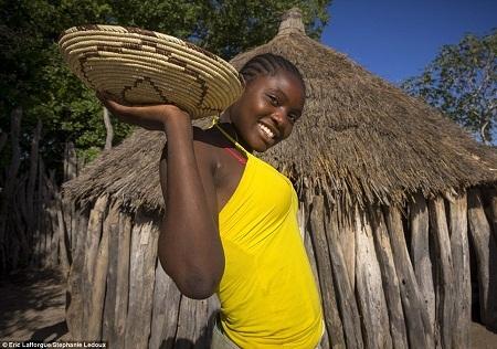 Một cô gái Okwanyama và chiếc giỏ mây đựng đầy bột mì.