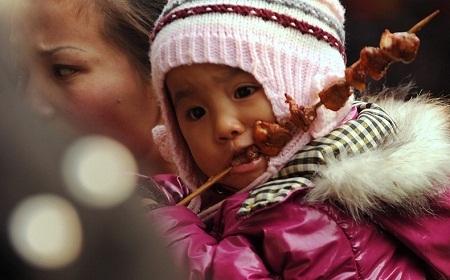 Một em bé ở Bắc Kinh, Trung Quốc đang ăn thịt xiên nướng. (Ảnh: Peter Parks)
