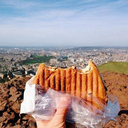 Ăn bánh kẹp khi đang leo núi ở thành phố Edinburgh, Scotland.