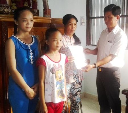 Ông Hồ Thanh Nghĩ- Phó phòng LĐ-TB&XH huyện Vĩnh Lợi trao quyết định bàn giao nhà cho chị Ngọc.