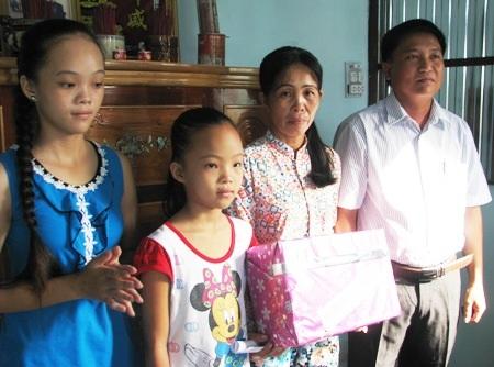 Đại diện chính quyền địa phương thị trấn Châu Hưng tặng quà cho 3 mẹ con chị Ngọc.