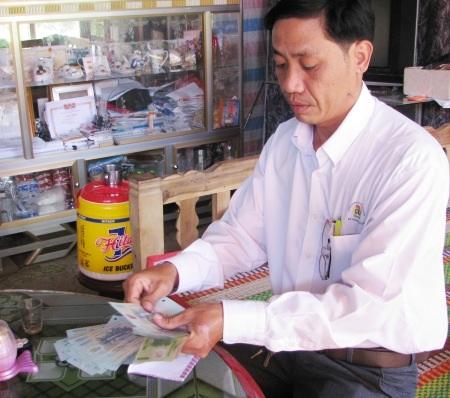 Đại diện địa phương kiểm đếm lại số tiền bạn đọc ủng hộ cho gia đình em Diễm.