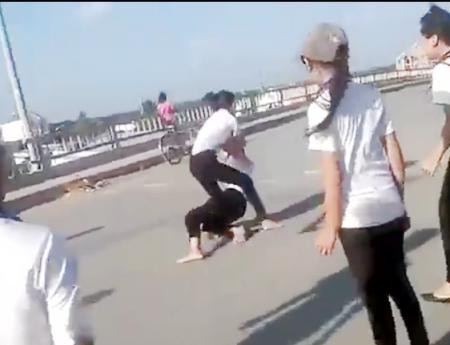 Hai nữ sinh đánh nhau có sự cổ vũ của nhiều học sinh khác.