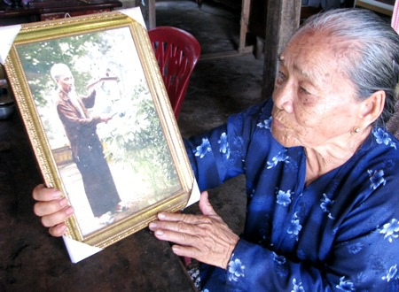 Bà Nguyễn Thị Bảy (con dâu má Tư) nâng niu bức ảnh Bác Hồ tưới cây vú sữa.