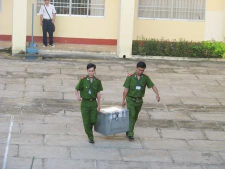 Lực lượng công an mang thùng chứa đề thi vào điểm thi.