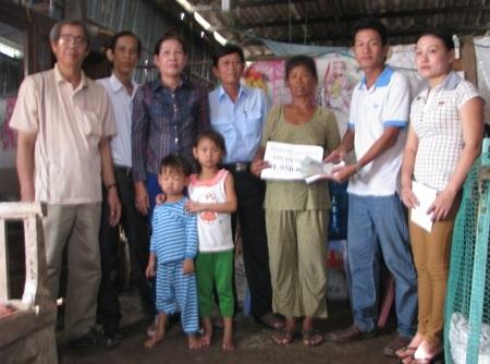 PV Dân trí và đại diện ban ngành địa phương cùng trao tiền bạn đọc đến bà cháu bà Kim Thị Phượng.