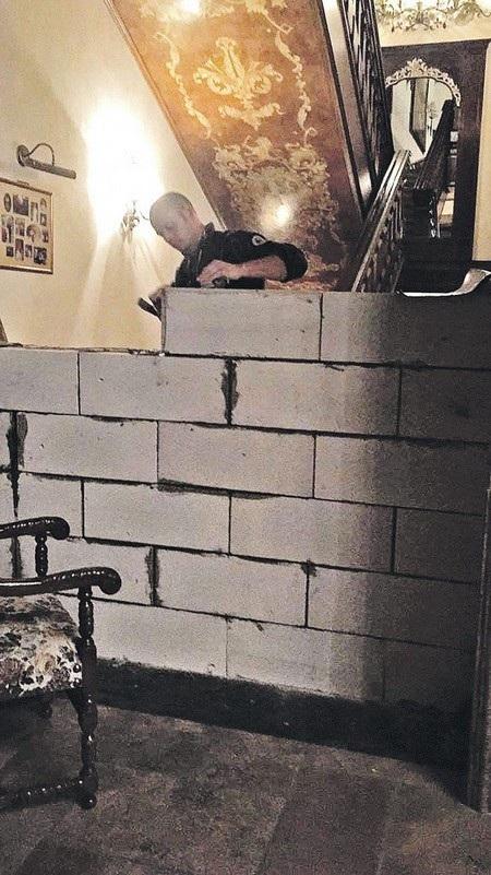Một công nhân xây dựng đang xây bức tường để chia đôi căn nhà. Phần cầu thang nằm ở phía nửa căn nhà của người chồng
