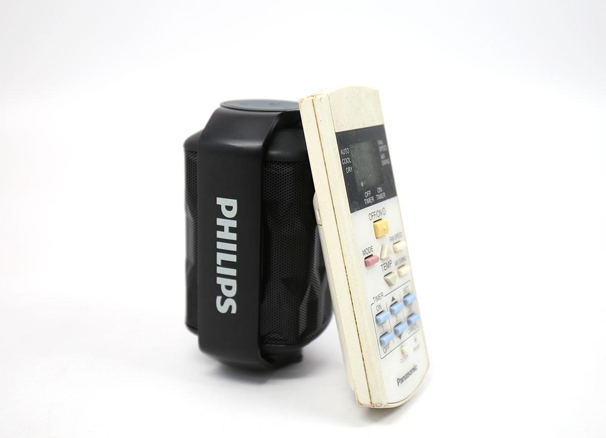 Loa Philips SHOQBOX mini BT2200 khá nhỏ bên cạnh một chiếc remote máy lạnh