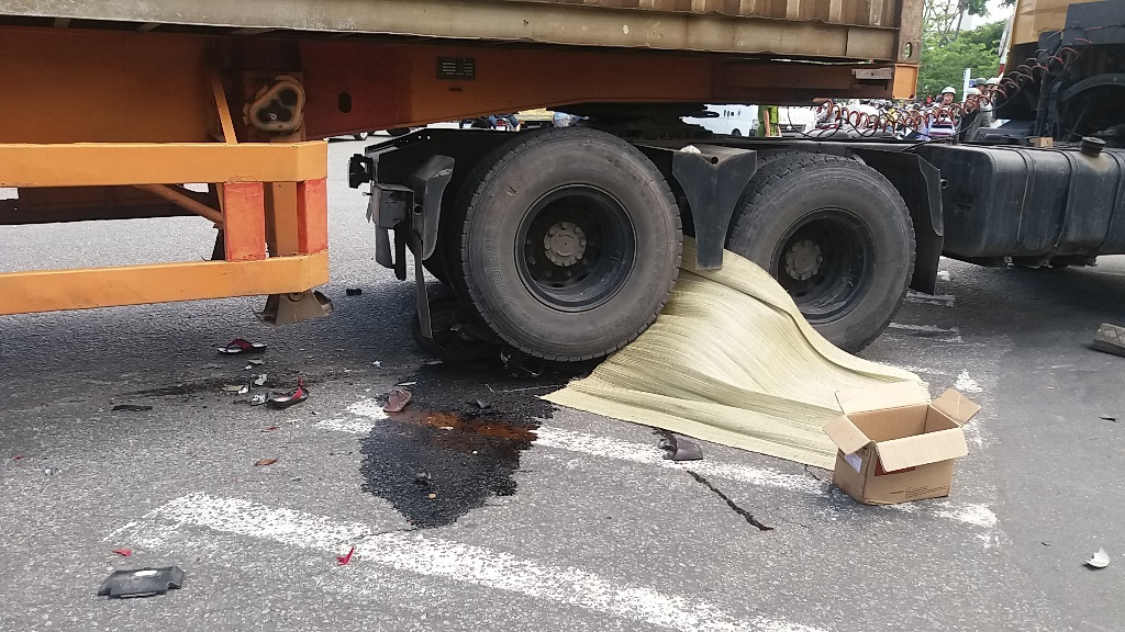 Cả xe máy và người đều bị kẹt giữa 4 bánh xe container