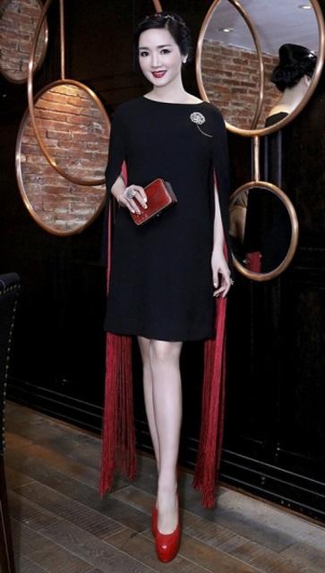 """Giáng My khoe vẻ đẹp """"không tuổi"""" trong bộ trang phục nền nà, chín chắn với 2 tông màu đen – đỏ nổi bật giúp người đẹp khoe đôi chân thon dài và làn da trắng nõn. Phụ kiện đồng màu, họa tiết tua rua hợp mốt cũng là điểm cộng lớn cho bà mẹ một con."""