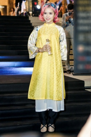 Suni Hạ Linh kết hợp áo dài cách tân với mốt giày vải đan dây. Nữ ca sĩ khiến khán giả thích thú khi dung hòa màu tóc hồng rực hiện đại và nét đẹp truyền thống của tà áo dài.