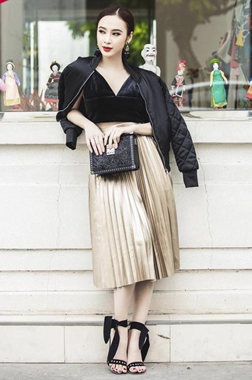 Angela Phương Trinh khoe làn da trắng trong bộ cánh với 2 tông đen-vàng – sự kết hợp đang khuynh đảo các sàn diễn thời trang năm 2017. Người đẹp phối áo crop-top nhung với chân váy xếp li, đi cùng là giày cột dây bản to, túi xách và hoa tai cực kì sang trọng.