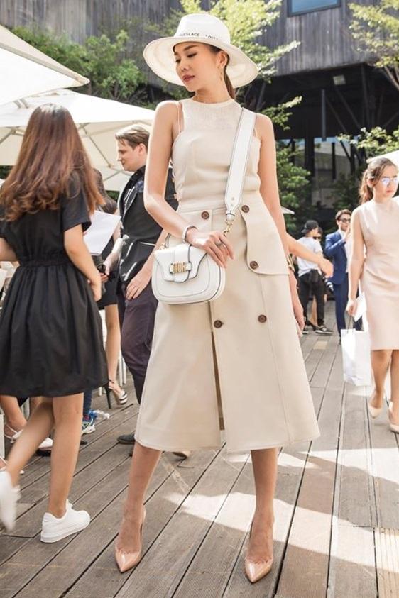 Thanh Hằng diện trang phục mang hơi hướng cổ điển. Người đẹp kết hợp nón rộng vành, đầm liền nhiều nút đậm chất châu Âu và sành sỏi tạo thêm điểm nhấn bằng chiếc túi hàng hiệu đồng màu.