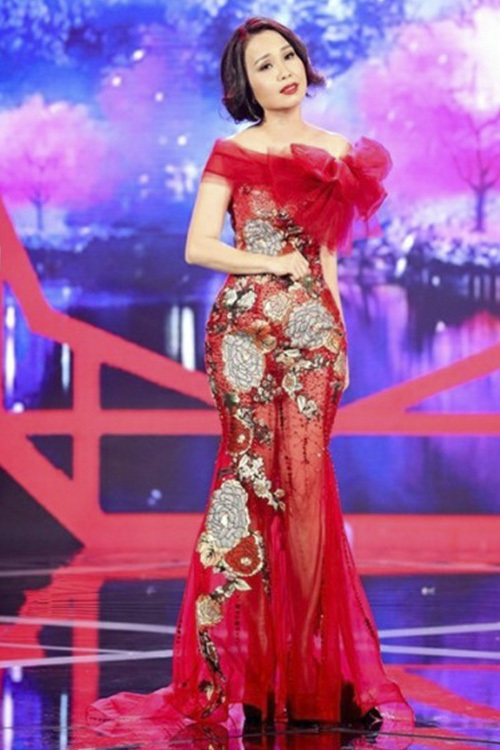 """""""Chị Tư"""" Cẩm Ly diện đầm đỏ với họa tiết hoa bản to, bẹt vai, thắt nơ sến sẩm và cực kì rối mắt. Mái tóc """"bến Thượng Hải"""" cũng như đôi giày đen """"chỏi mắt"""" cũng là những điểm trừ cho nữ ca sĩ."""