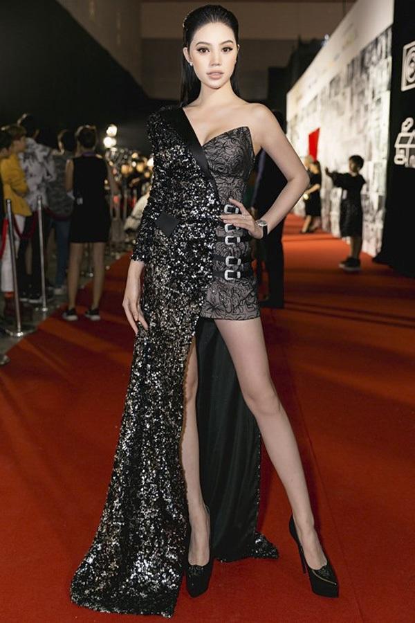 """Jolie Nguyễn trung thành với phong cách trang điểm tông nude. Người đẹp thể hiện độ """"chịu chi"""" khi chọn bộ váy quay ôm sát, khoác ngoài lớp áo choàng bất đối xứng lạ mắt với trị giá hàng trăm triệu đồng."""