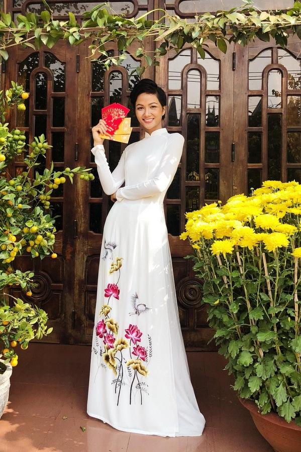 Hoa hậu Hoàn vũ 2017 H'Hen Niê trung thành với tà áo dài truyền thống. Người đẹp diện cây trắng tinh khôi với hoạ tiết hoa sen, chim hạt nịnh mắt. Cô nàng trang điểm nhẹ nhưng vẫn rất nổi bật.