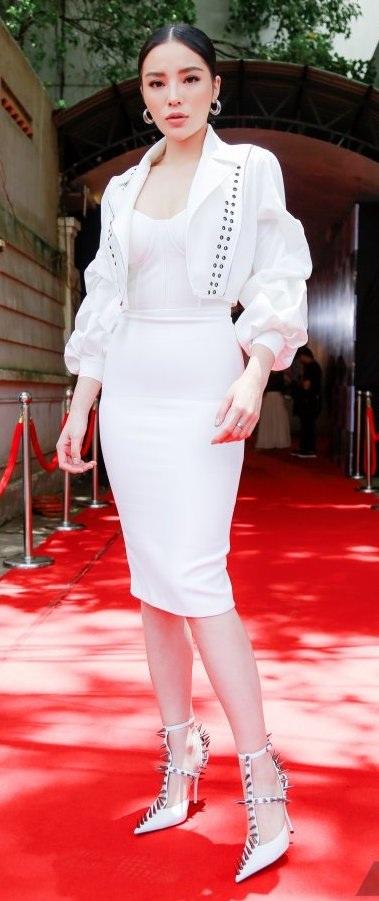 Kỳ Duyên diện đầm bodycon sáng màu, kết hợp cùng áo khoác tay bồng kiểu bá tước và giày đinh tán, vừa cá tính vừa quyến rũ.