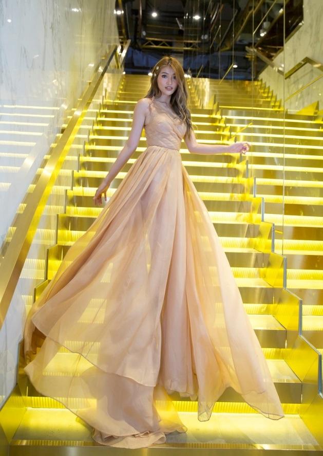 Chiếc đầm dài màu vàng nhạt với phần thân váy xòe rộng tạo cảm giác bồng bềnh, thanh thoát.